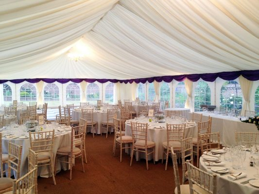 white and purple wedding in a clearspan tent
